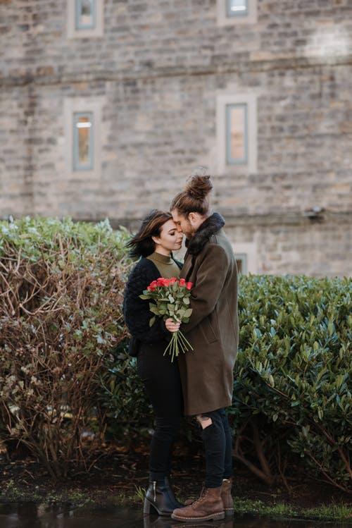 Side view of young hipster man embracing gently female beloved with rose bouquet on street