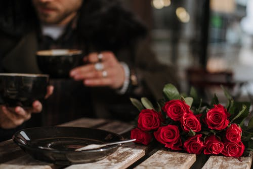 Crop unrecognizable man and woman in stylish outfit drinking coffee in street cafe sitting at table with bunch of elegant red roses