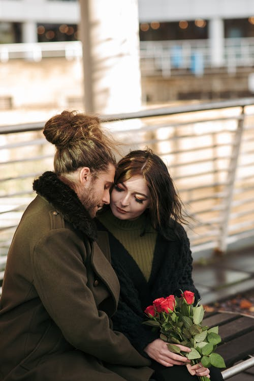 High angle of young enamored trendy guy with stylish outfit in coat hugging girlfriend while sitting together on wooden bench in park with bouquet if red roses