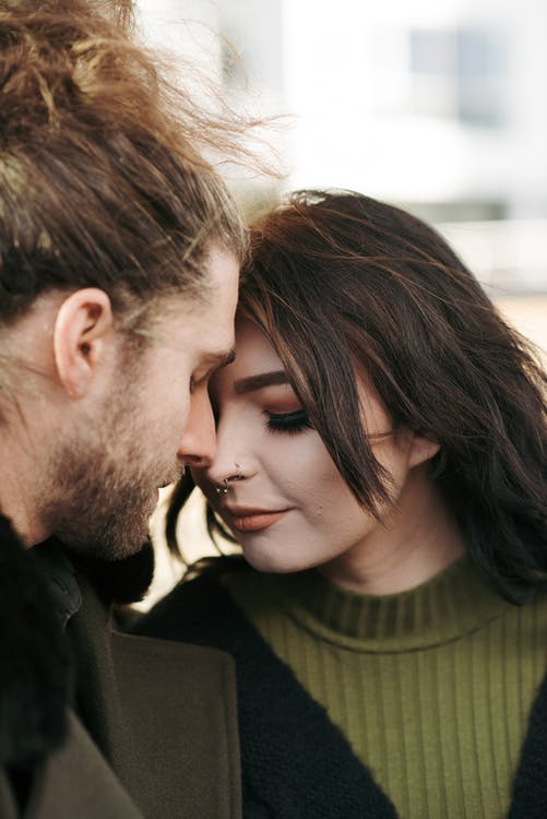 Loving young couple in stylish outfits touching foreheads with closed eyes on city street in daytime