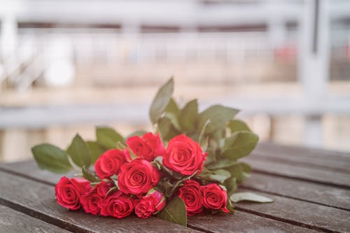 Fragrant roses placed on wooden table on street