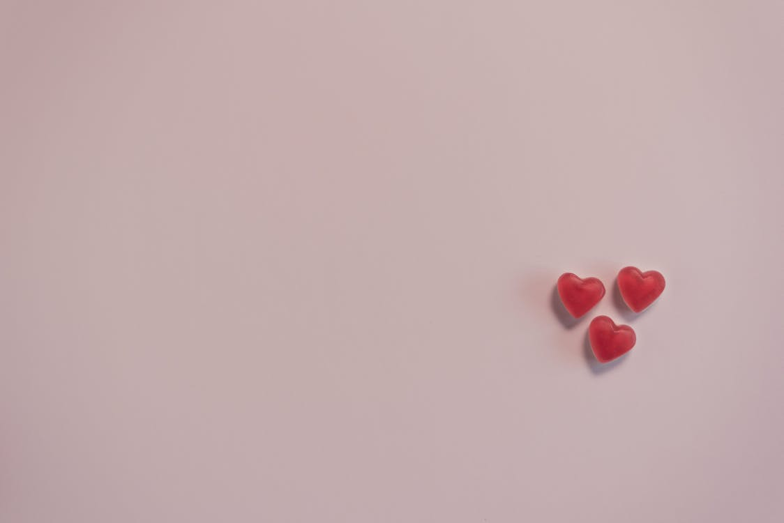 Small red heart shaped candies on pink surface