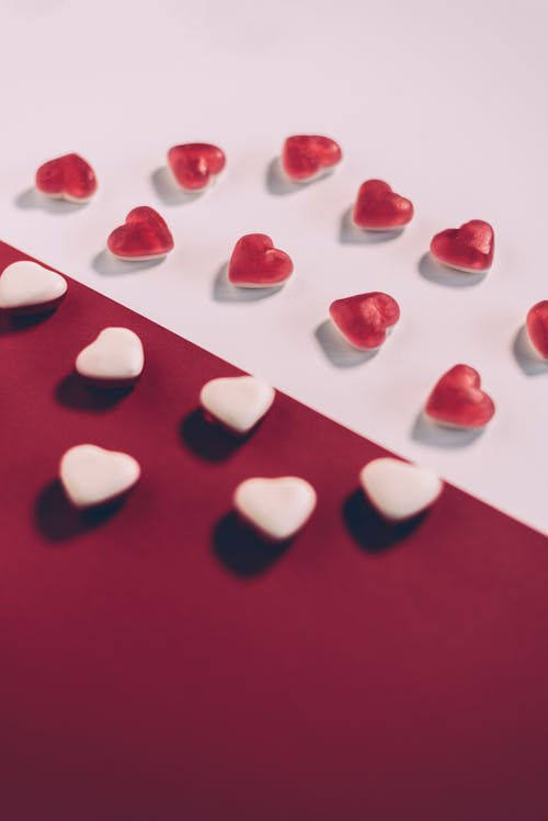 From above arrangement of white and red heart shaped candies placed on multicolored background during saint valentine day celebration in studio