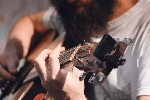 Crop faceless man with beard holding modern acoustic guitar and playing during concert