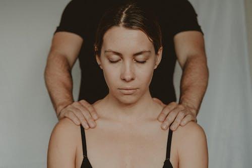 Crop man touching shoulders of woman