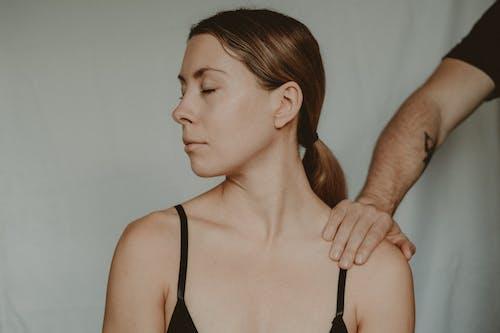 Crop man touching shoulder of woman