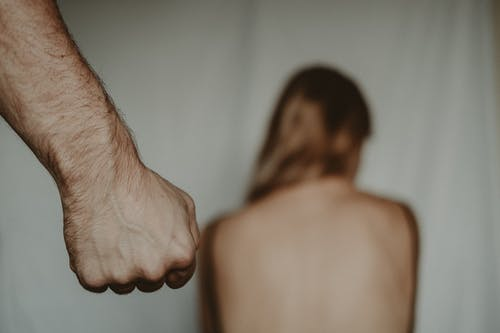 Aggressive abusive anonymous man clenching fist while insulting unrecognizable vulnerable female sitting on blurred background in light room during violence