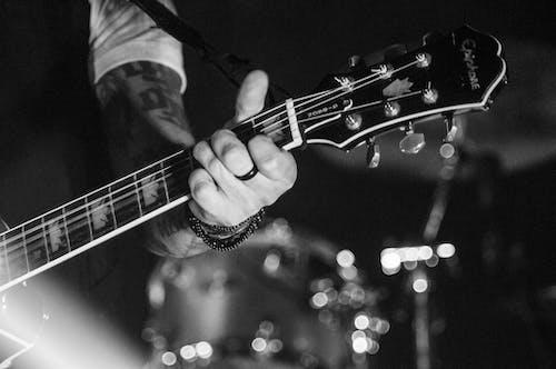 Crop man playing guitar on concert