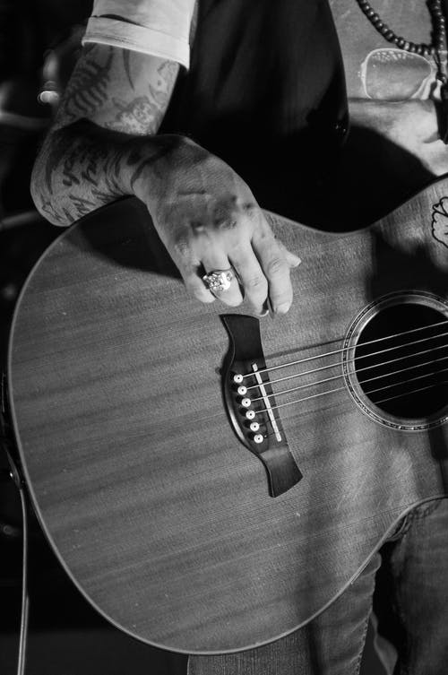 Black and white of crop unrecognizable man with tattoos playing acoustic guitar during rehearsal