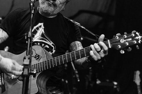Black and white of crop unrecognizable male with beard and tattoos playing acoustic guitar on stage during concert
