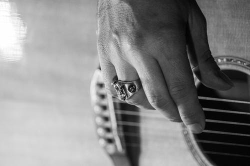 Black and white of crop anonymous male with ring playing acoustic guitar while practicing