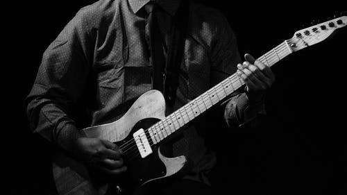 Black and white of crop anonymous male musician playing electric guitar while rehearsing in studio