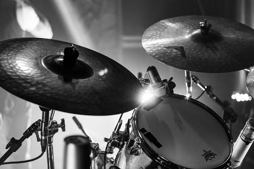 Black and white of drums under bright lights on stage during rock concert