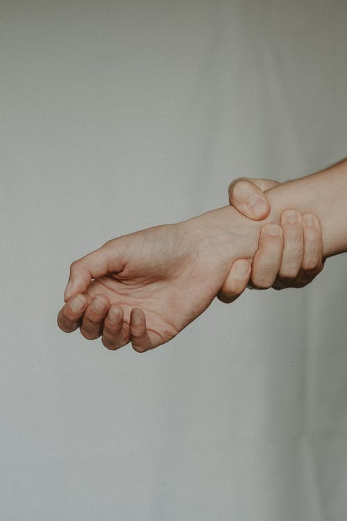 Unrecognizable person holding tight wrist of anonymous person trying to stop on grey background
