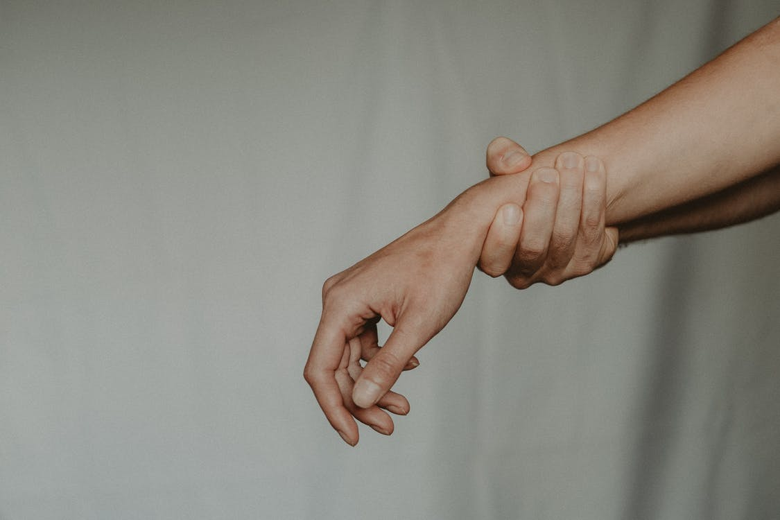 Unrecognizable person holding hand of partner abusively