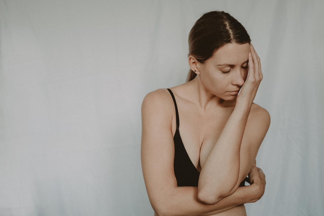 Young slender female in black bra standing with closed eyes covering face with hand