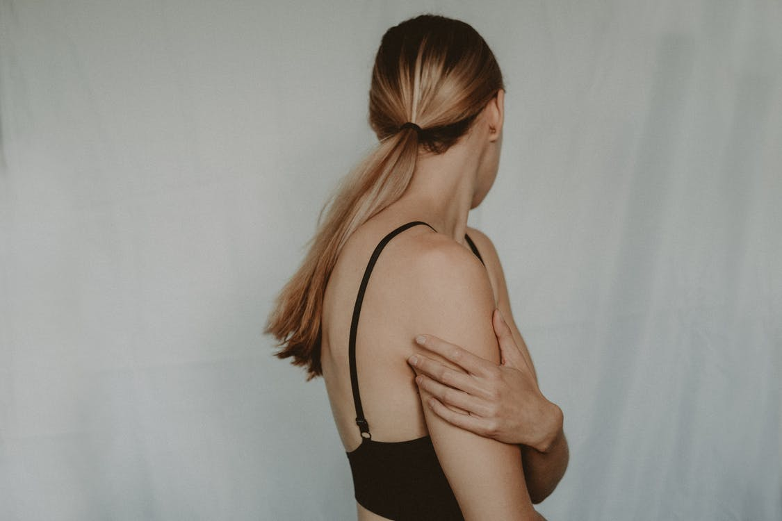 Side view of unrecognizable young female with long hair and black bra standing near grey wall turning head away