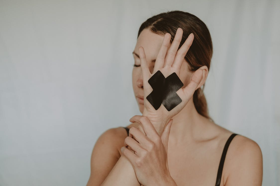 Young woman in black lingerie with closed eyes demonstrating hand with black tape cross against violence on white background