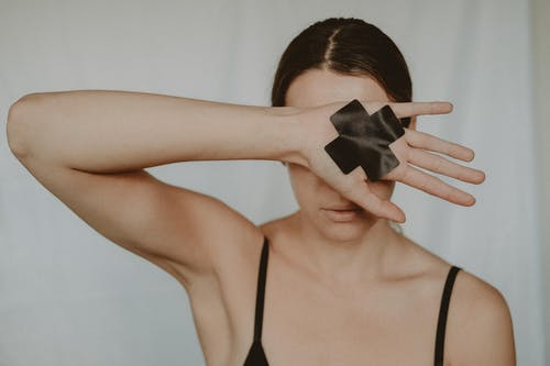 Faceless young lady in black underwear showing hand with black cross tape against abuse on white background