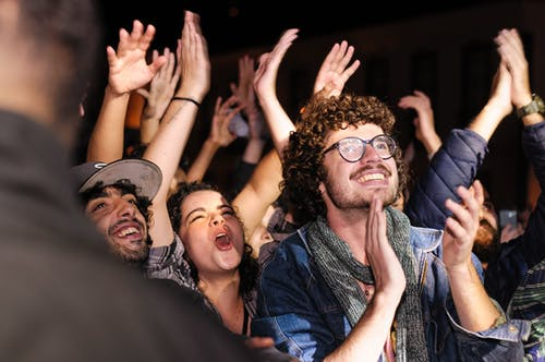 Joyful audience raising and clapping hands at party