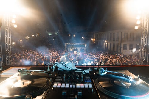 DJ console at stage with crowded audience