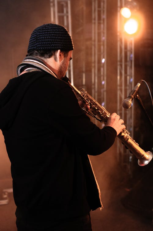 Side view of talented male playing saxophone while standing on stage with microphone in bright light