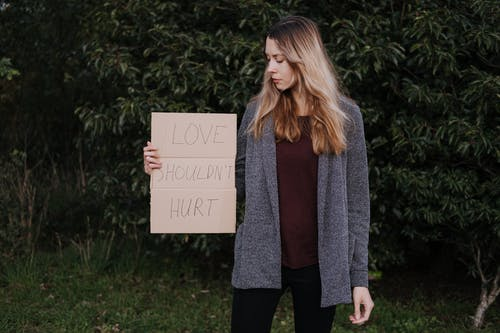 Female demonstrating cardboard with words against abuse