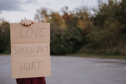 Crop anonymous person demonstrating carton signboard with slogan love should not hurt on blurred background of asphalt road and trees