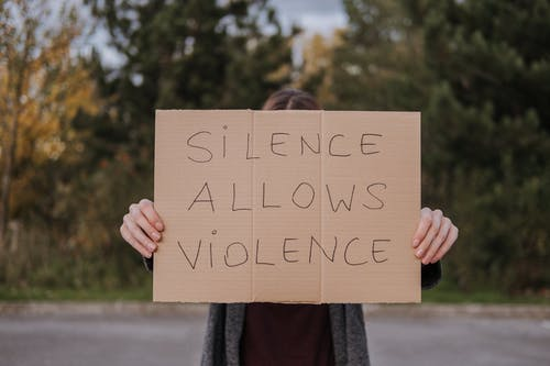 Anonymous person showing slogan silence allows violence on cardboard on road near green trees