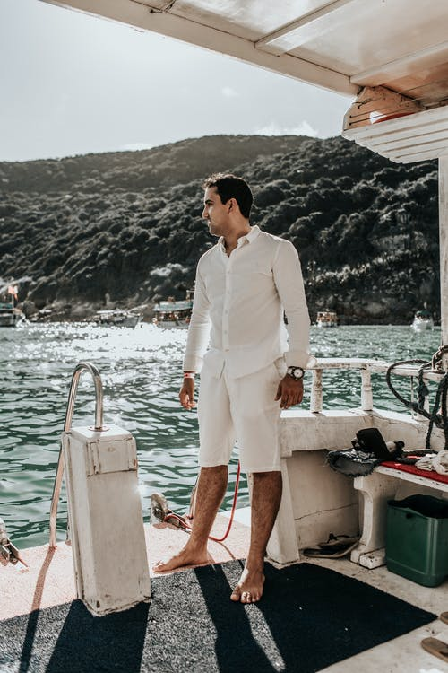 Man in White Suit Standing on Boat