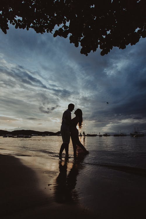Couple Kissing on Beach during Sunset