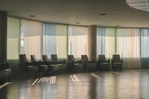 Interior of empty room with armchairs placed in row near windows closed with blinds