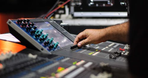 Unrecognizable male sound operator turning switches on control panel with monitor and channel faders while working in professional recording studio