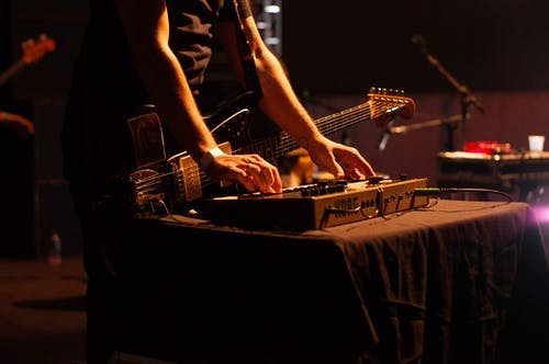 Crop guitarist playing synthesizer during concert