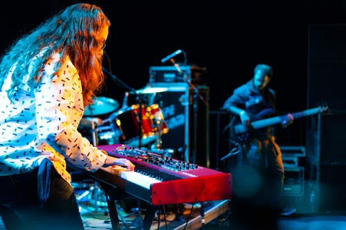 Talented musician playing melody on synthesizer while performing song on stage with drum set and musical equipment near guitarist during concert