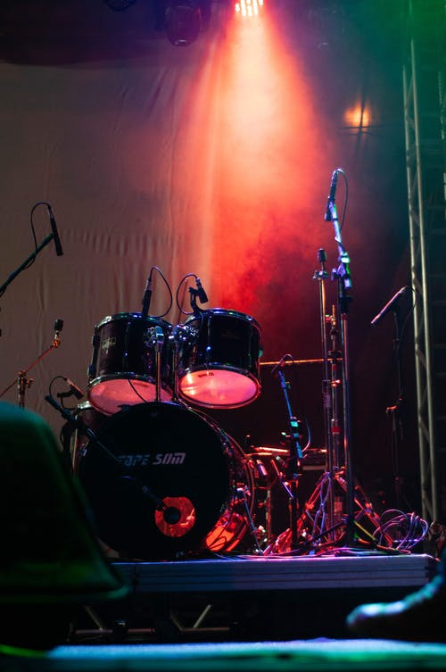 Modern professional drum set placed near wall on obscure stage with microphone stands under bright red light during live concert