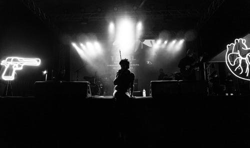 Black and white of talented anonymous artist sitting on dark stage with bright spotlights while performing song during live concert