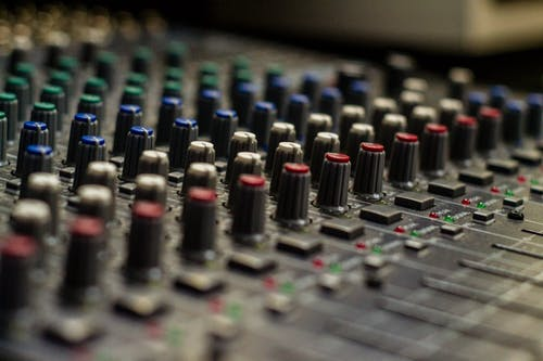 Sound mixer with rows of knobs in recording studio