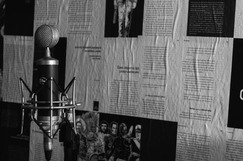 Black and white of aged mic on stand against wall with paper representing photos and text in columns