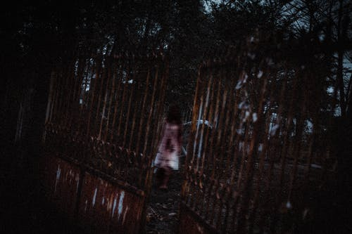 Anonymous creepy ghost woman in white bloody dress walking in dark cemetery near old rusty metal gates