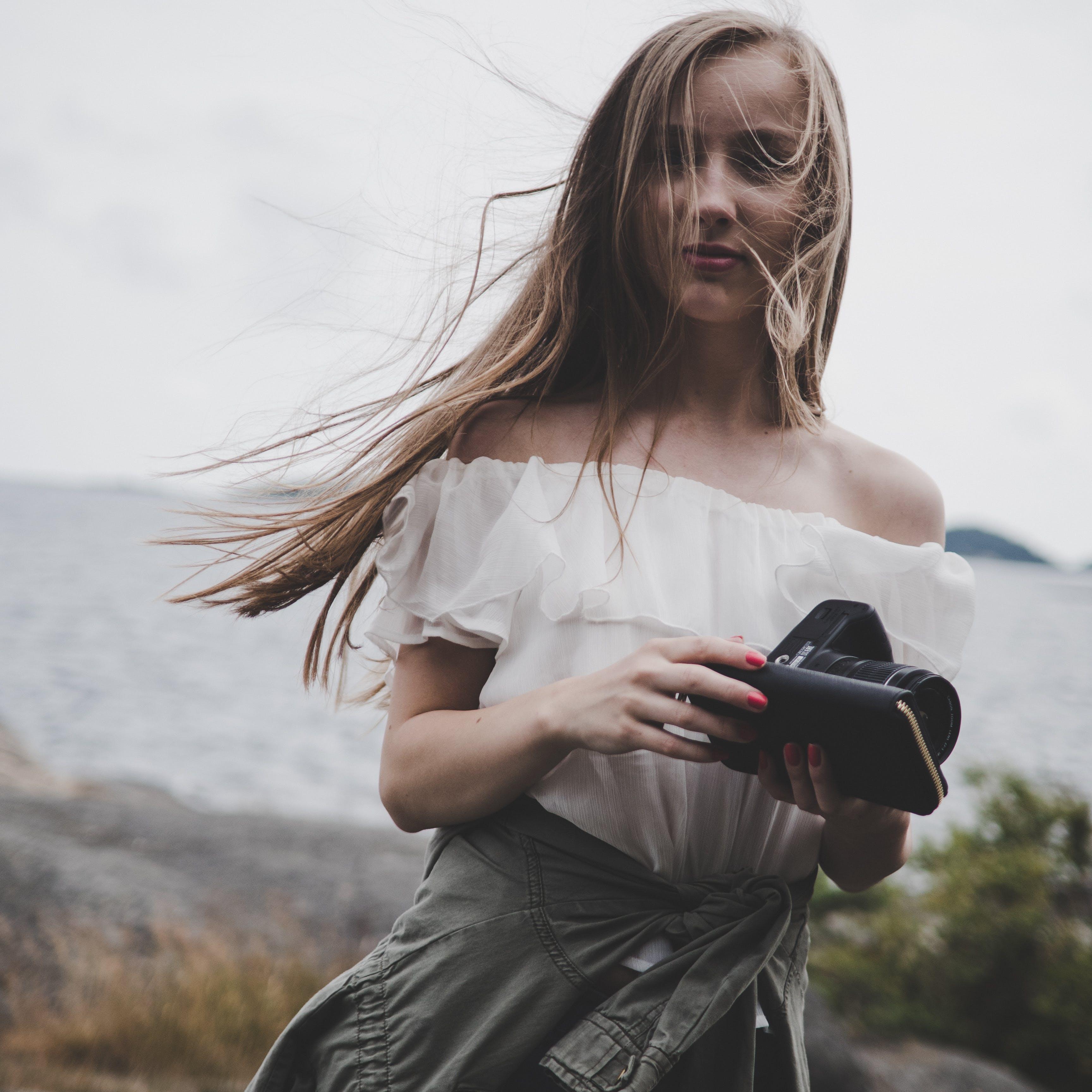 Woman Sitting on Seashore Holding Camera