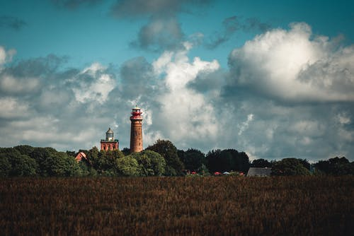 Brown and White Lighthouse Under Blue Sky and White Clouds