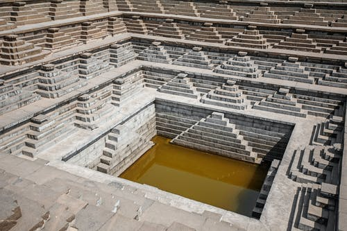 From above or stone rows of stairs of stepped well with dirty water in Hampi India