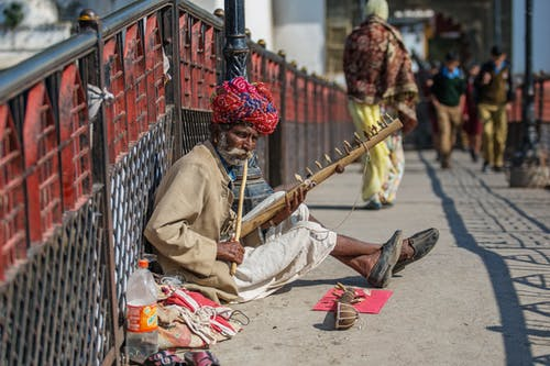 Poor Indian man in turban playing traditional dilruba instrument sitting on street collecting money