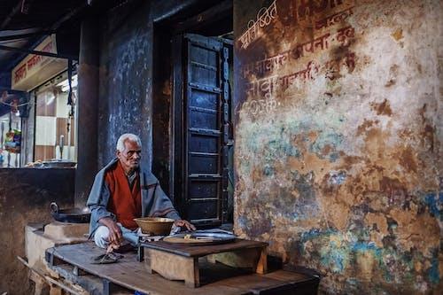 Elderly ethnic man on local street bazaar