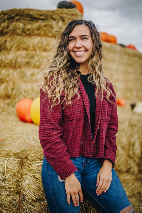 Smiling Woman in Red Button Up Long Sleeve Shirt and Blue Denim Jeans
