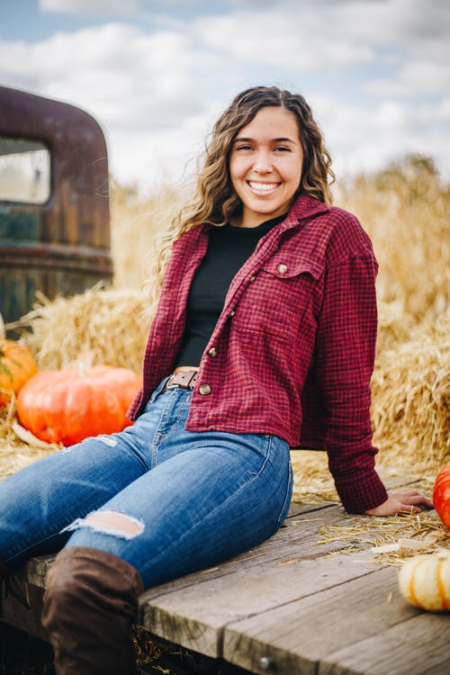Woman in Red Knit Sweater and Blue Denim Jeans Sitting on Brown Wooden Bench