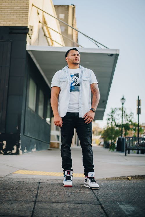 Man in White Crew Neck T-shirt and Black Pants Standing on Gray Concrete Floor during