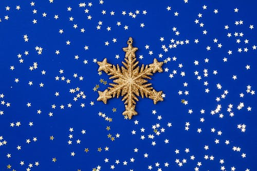 Gold Stars and Gold Snowflake on Blue Background