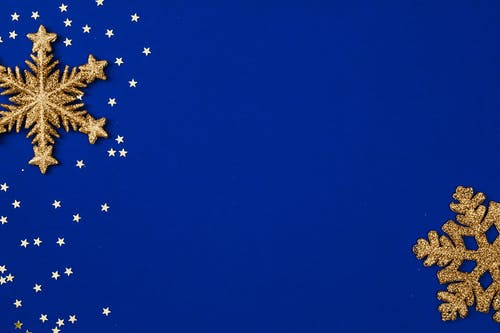 Gold Stars and Gold Snowflakes on Blue Background